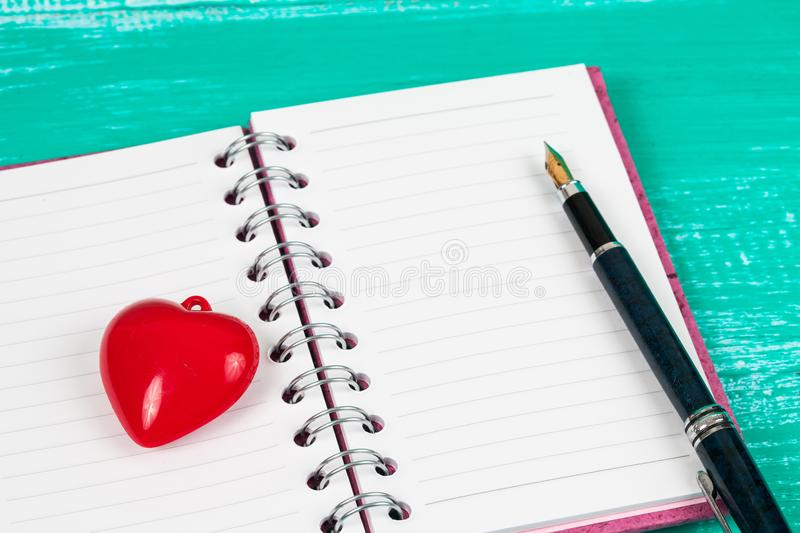 Red heart sign on book note in wood table. Background stock photos