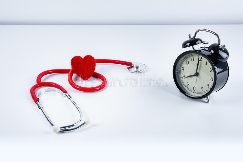 Red heart and stethoscope, alarm clock on table royalty free stock photos