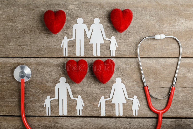 Red heart, stethoscope and paper chain family on wooden table royalty free stock photos