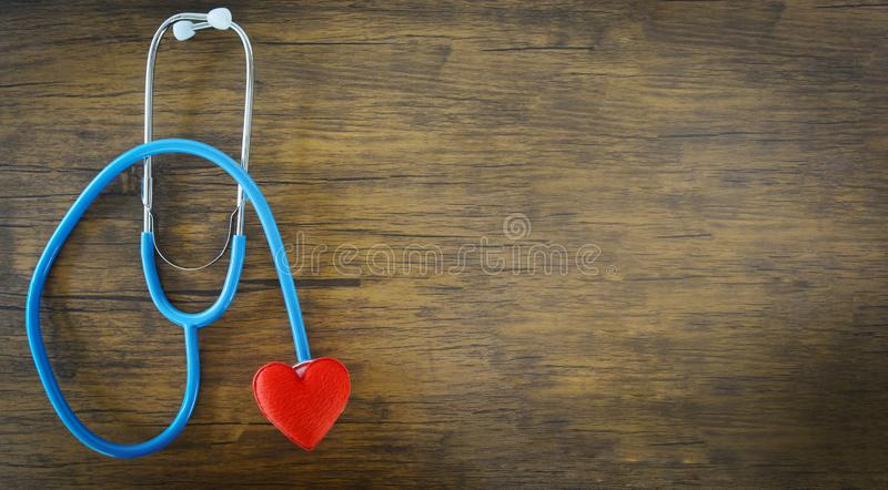 Red heart on stethoscope on wooden background / Check the heart medical for doctor is the patient pulse health concept. Red heart on stethoscope on wooden royalty free stock image