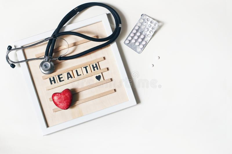 Red heart stone, stethoscope, wooden letter board and pills on white table background. Medical examination, treatment. Health care, heart diseases and stock photography