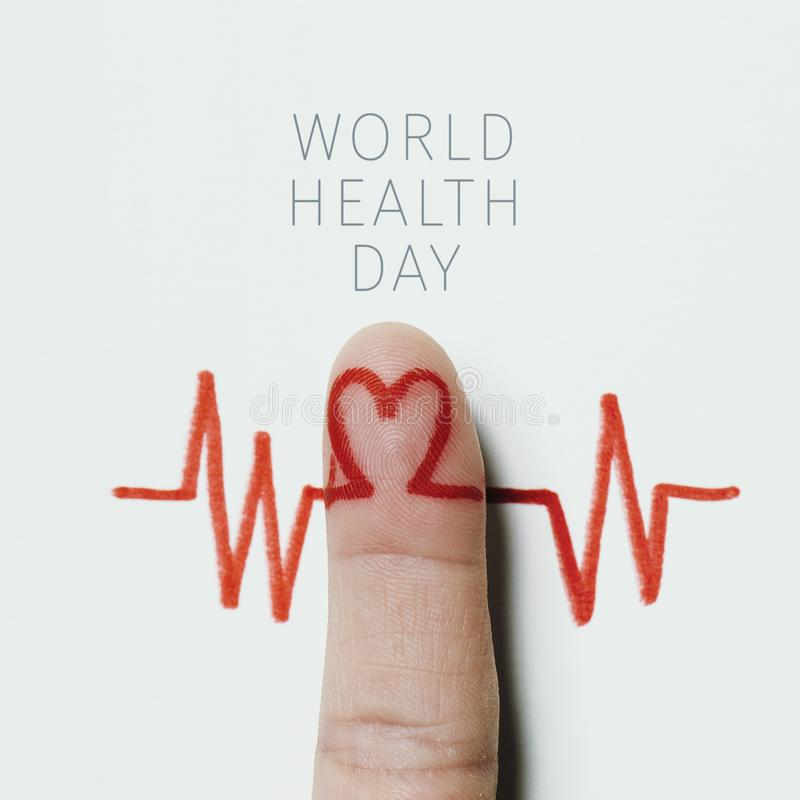 Heart symbol and the text world health day. A red heart symbol in the forefinger of a man as in an electrocardiogram painted on a white background and the text stock photography