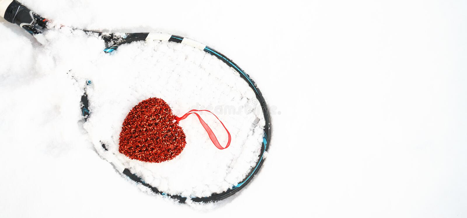 Red heart on tennis racket on white snow winter background. I love you tennis player on Valentine`s day. concept with tennis play. royalty free stock photos