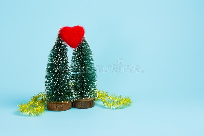 Red heart between two Christmas trees stock photo
