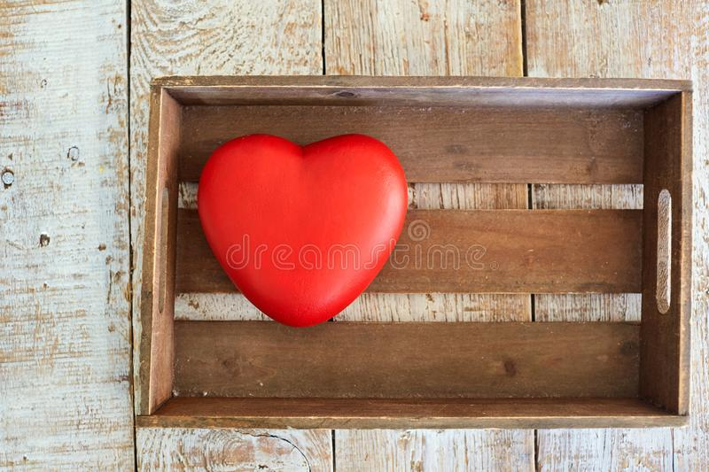 Red heart in a wooden box on the table. stock photography