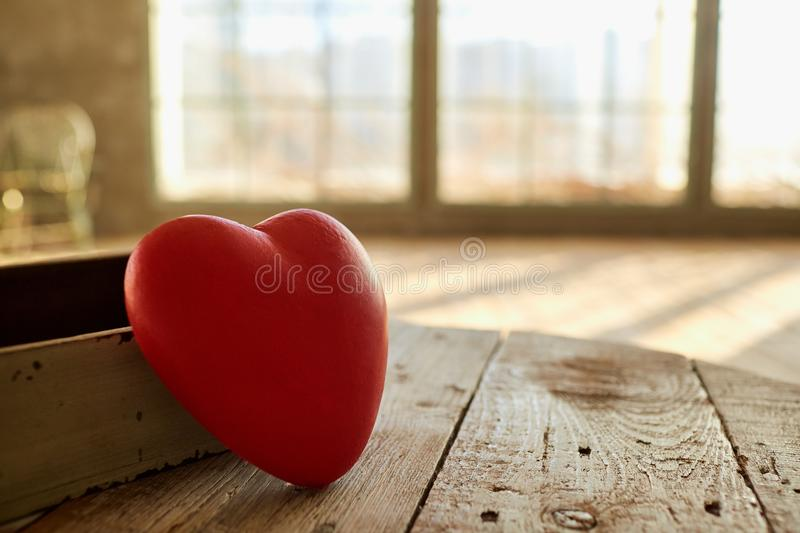 Red heart on a wooden table in front of a window. stock photography