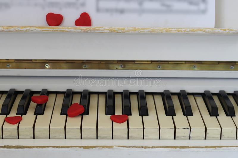 Red hearts adorn piano keys Valentine`s Day . Red hearts adorn piano keys. Valentine`s Day royalty free stock photography
