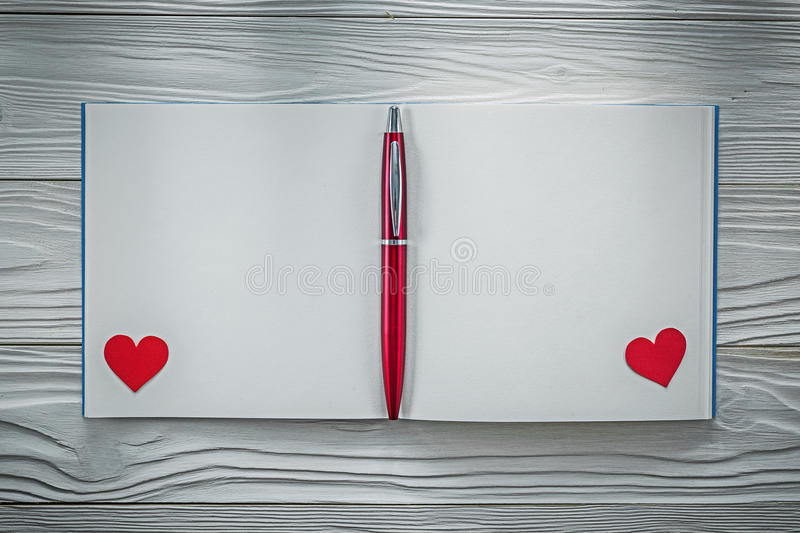 Red hearts ball-point pen clean notebook on wood board education. Concept stock photos