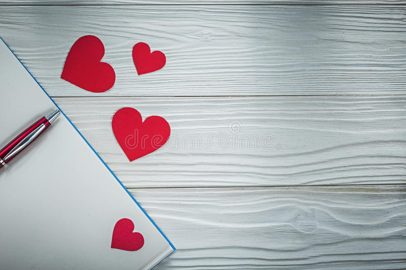Red hearts ball-point pen clean notepad on wooden board educatio. N concept royalty free stock images