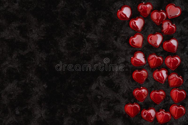 Red hearts on black rose textured plush fabric stock photography