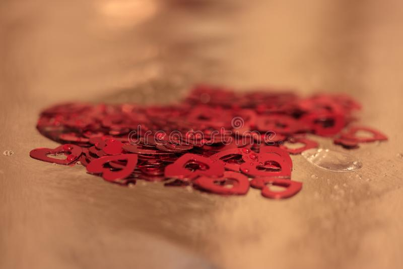 Red hearts confetti splashed with water droplets royalty free stock images