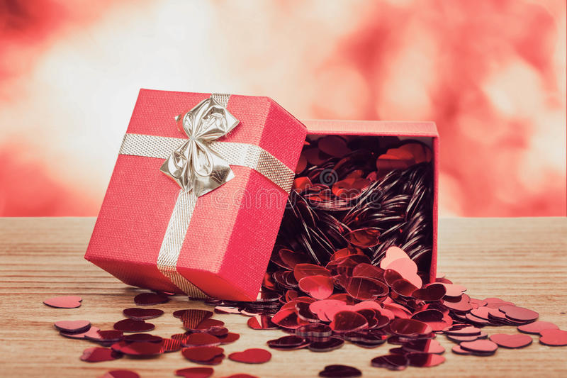 Red hearts confetti on wooden background and bokeh. Small red hearts confetti and present box on wooden background with bokeh royalty free stock photography