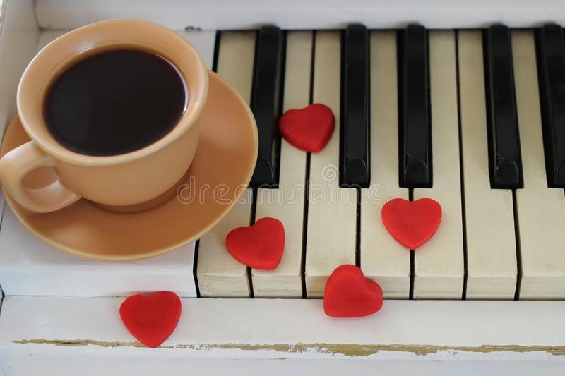 Red hearts and a cup of coffee are decorated with piano keys. Va. Lentine`s Day royalty free stock photos