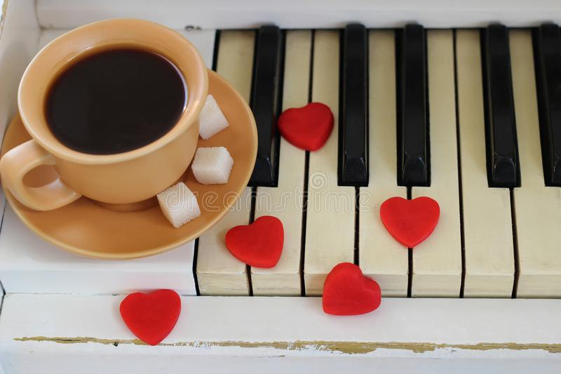 Red hearts and a cup of coffee are decorated with piano keys. Va. Lentine`s Day stock images