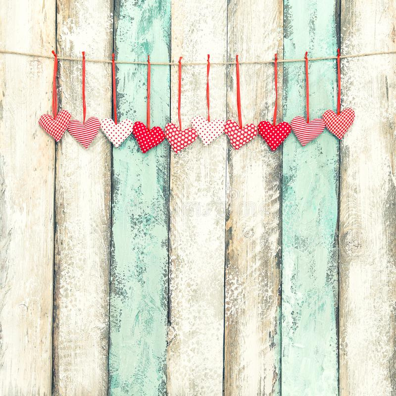 Red hearts decoration hanging Valentines day vintage style. Red hearts decoration hanging on wooden background. Valentines day. Vintage style toned picture stock photos
