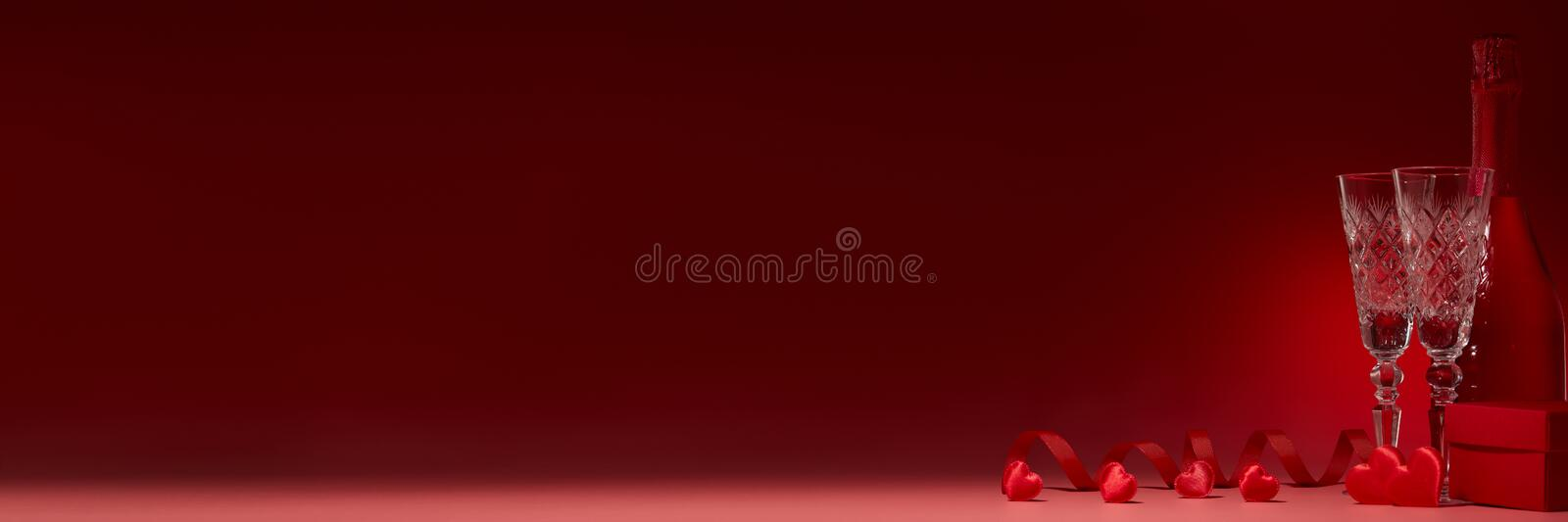 Champagne and flutes, gift box, red hearts on red background. Copy space. Valentine`s Day. Extra wide panorama banner background royalty free stock photos