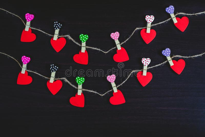 Red hearts hanging on rope on wood. Background stock image