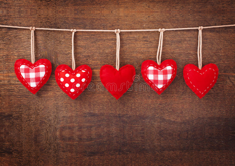 Red hearts hanging on wooden background stock images