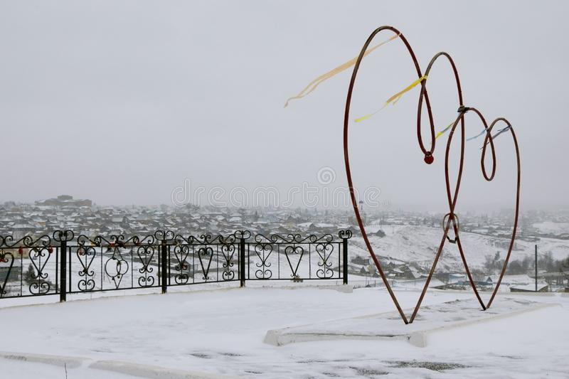 Red hearts from iron pipes in winter. In the wind in the winter of red heart pipes with locks. stock image