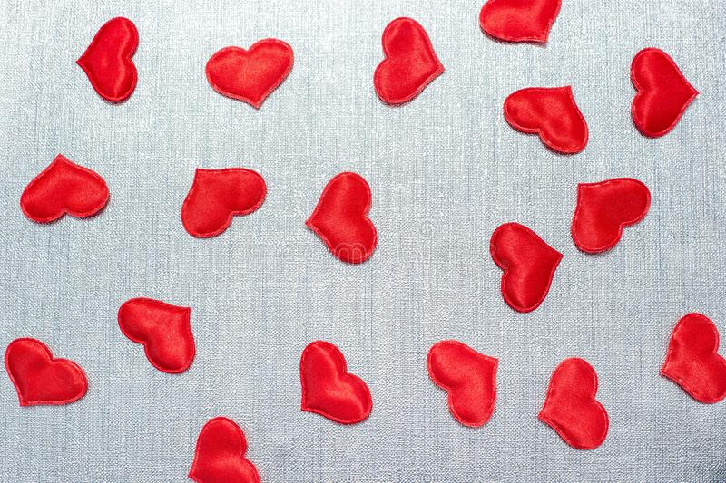 Red hearts lie on a silver background. Red hearts scattered on a silver background stock photo