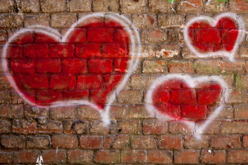 Red hearts painted on a brick wall. Original graffiti illustration of a heart of a brick wall royalty free stock photos