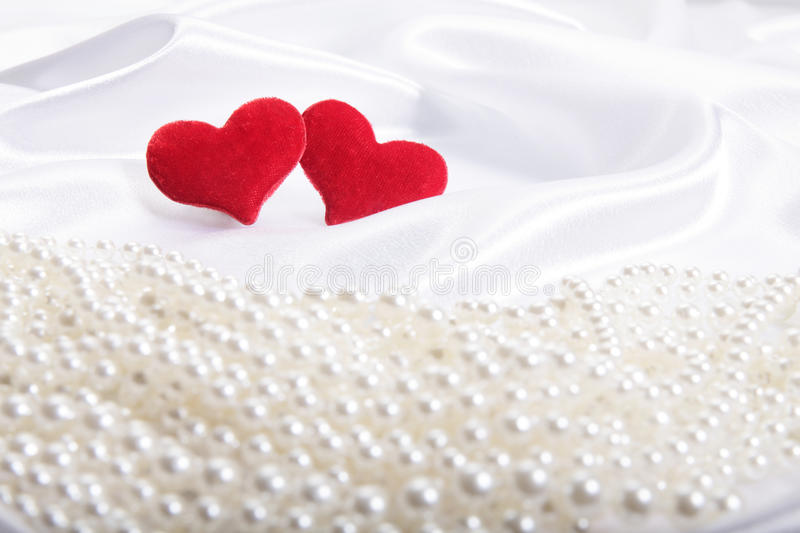 Red hearts on pearls background. Focus on hearts stock image