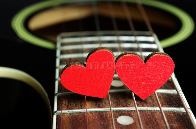 Red hearts on the strings of a guitar. Hearts are a symbol of love. Valentine`s Day royalty free stock photo