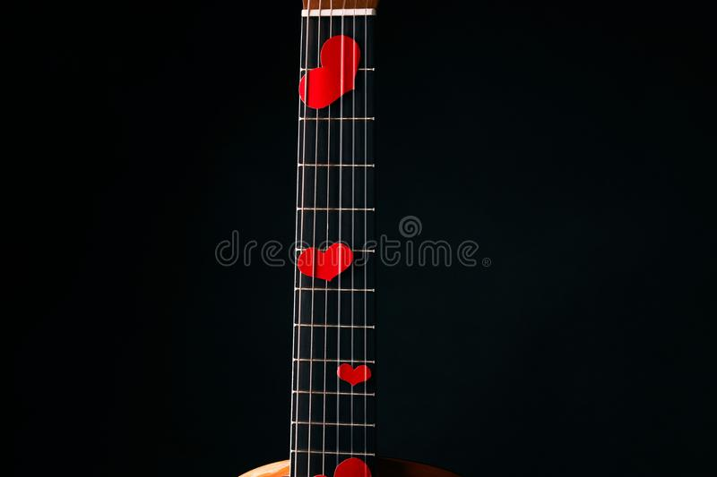 Red hearts on the strings of a guitar stock photography