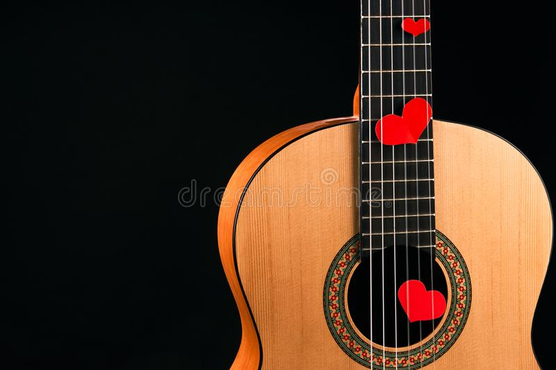 Red hearts on the strings of a guitar stock photo