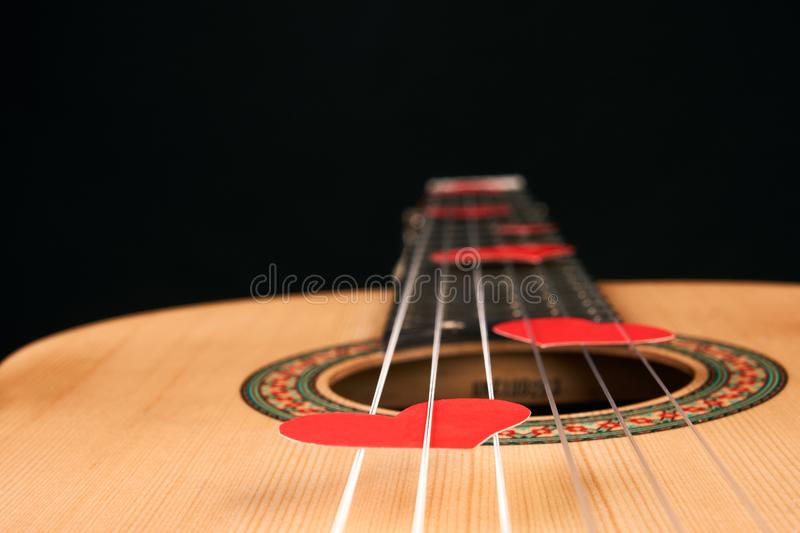 Red hearts on the strings of a guitar stock image