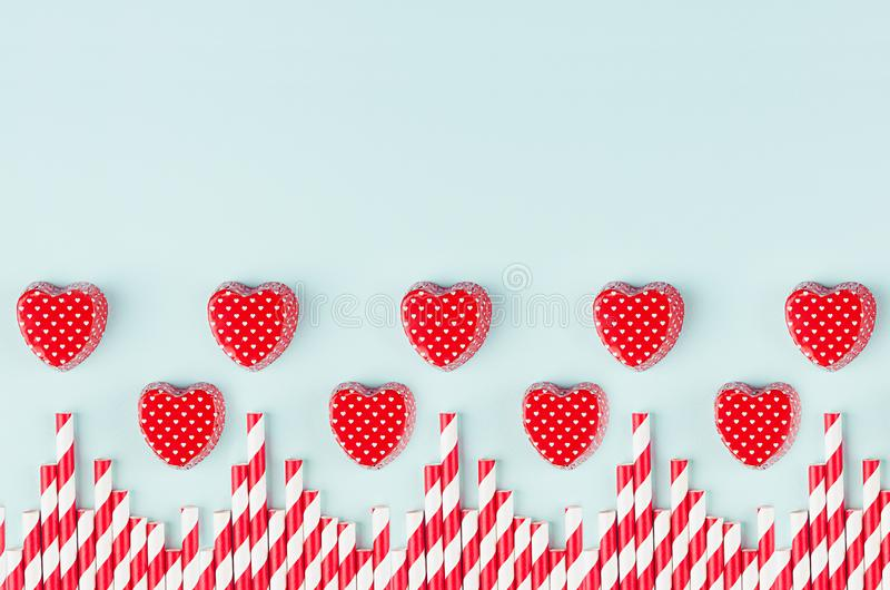 Red hearts and striped straws border with copy space on trendy color mint backdrop as playful modern valentine`s day background. Red hearts and striped straws stock images