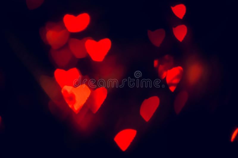 Red hearts texture. Red hearts bokeh in dark texture for use in graphic design. Valentines style defocused lights background. St. Valentine`s Day royalty free stock images