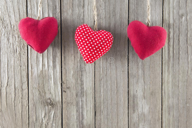 Red Hearts. Three red hearts on a wooden background stock image