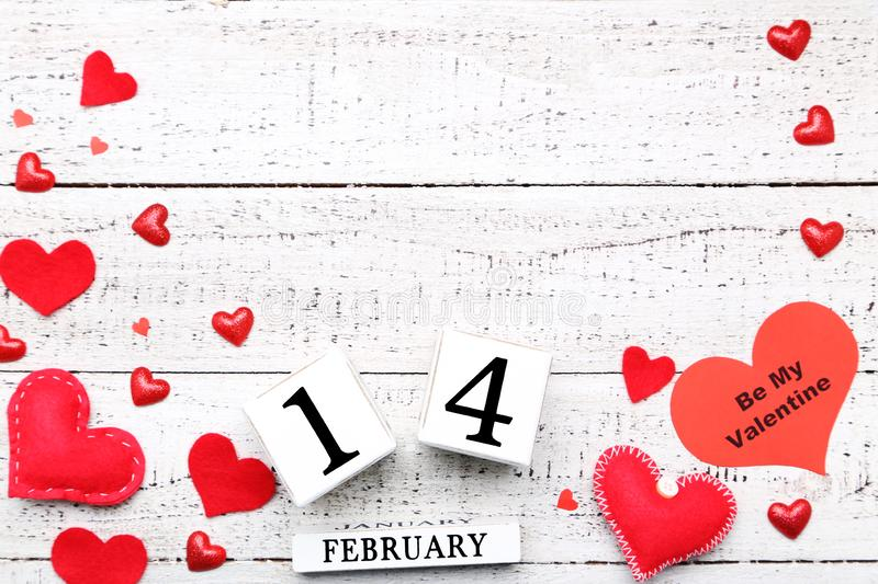 Hearts with wooden calendar. Red hearts with wooden calendar on white table royalty free stock photo