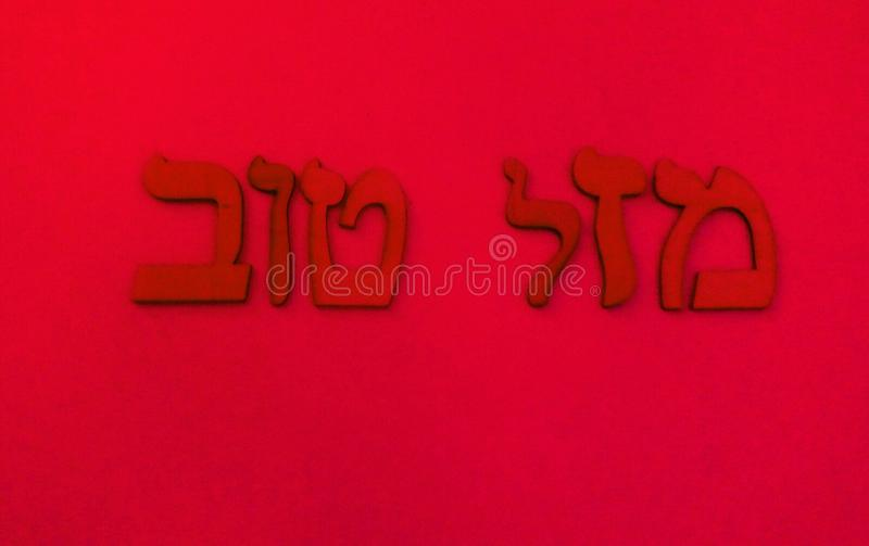 """Hebrew words. Red Hebrew words on red backround.In Hebrew""""Mazal Tov"""" and in English""""Good Luck"""" vector illustration"""