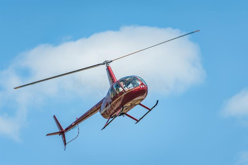Red helicopter against the blue sky performing at airshow royalty free stock photography