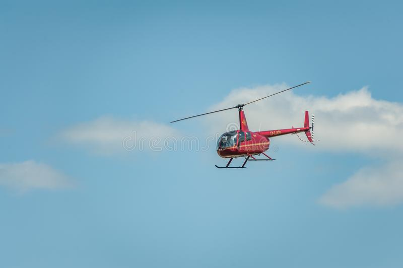 Red helicopter against the blue sky performing at airshow stock photos
