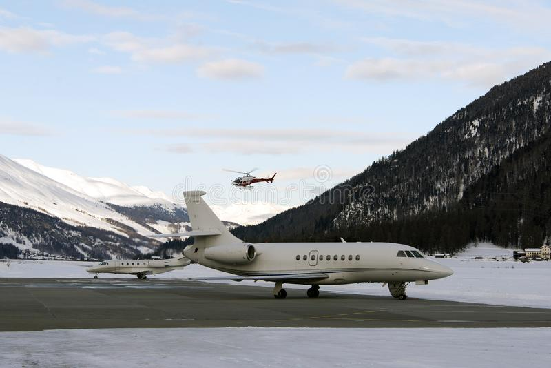 A red helicopter flying over two private jets in the airport of St Moritz Switzerland in winter stock photos