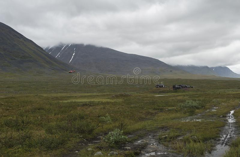 Red helicopter supply Hikers at Mountain Lodge Salka STF hut. Lapland mountain ladscape on summer cloudy day.  stock photo