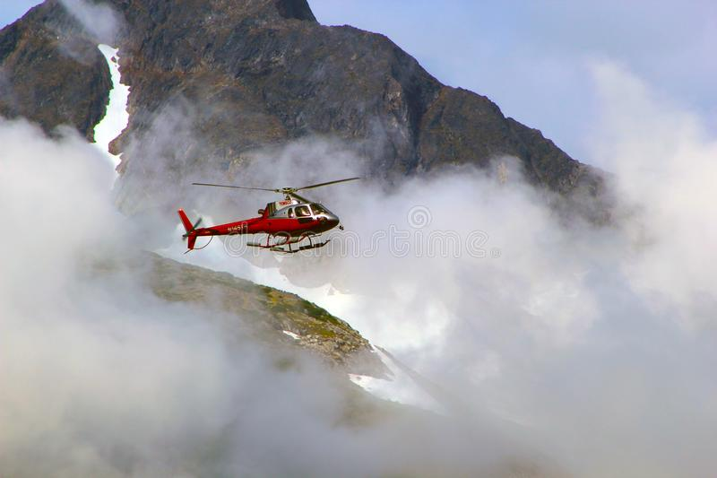 Red Helicopter on Top of Foggy Mountain stock images