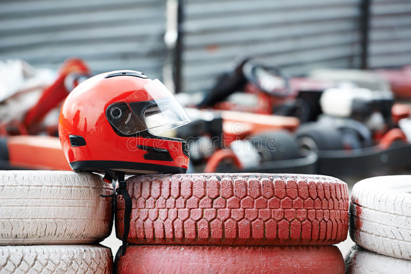 Red helmet with visor is on tires. By kartodrom royalty free stock image