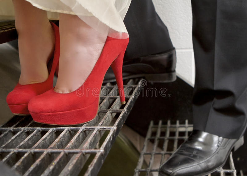 Red High Heels. Close-up of a couples feet standing on grated steps. She is in red high heels stock image