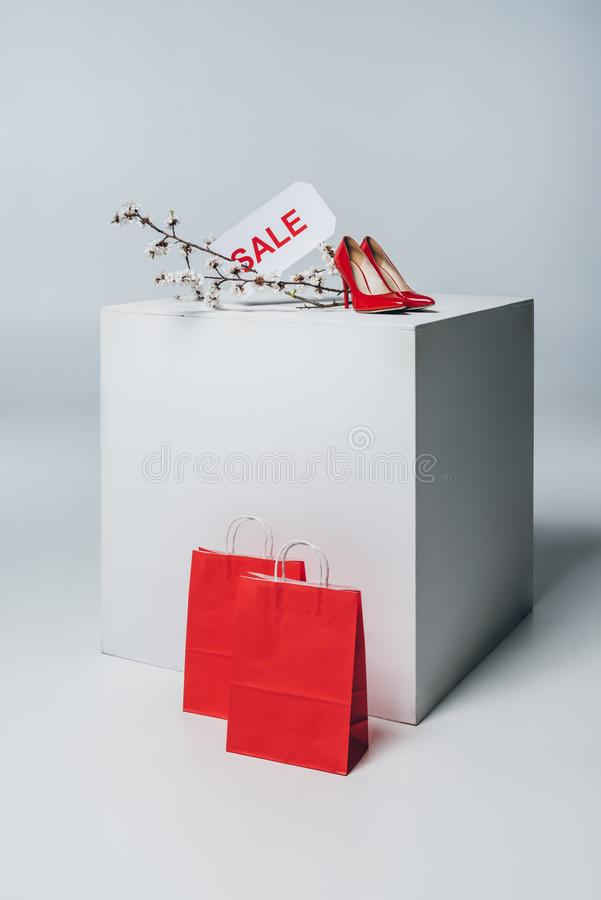 Red high heels with sale sign on white cube, summer. Sale concept stock image