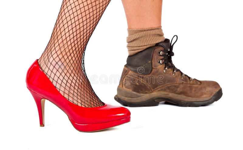 Red high hill shoe and brown walking boots. On a white background royalty free stock photos
