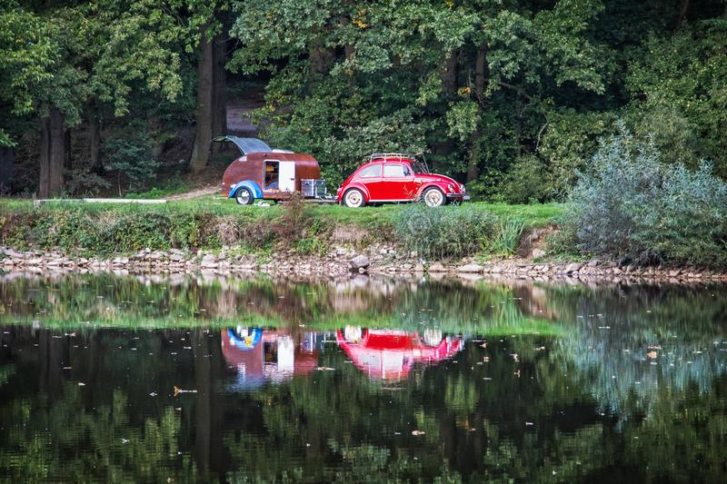 Red historic car with mini caravan is reflected in the lake. Travelling theme. Beautiful place stock photography