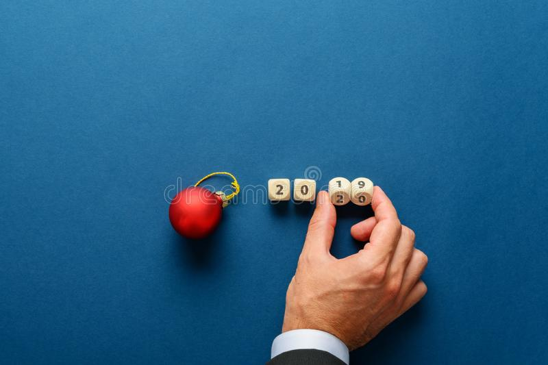 Red holiday bauble next to a 2019 sign on wooden dices with male hand changing it to 2020 royalty free stock photo