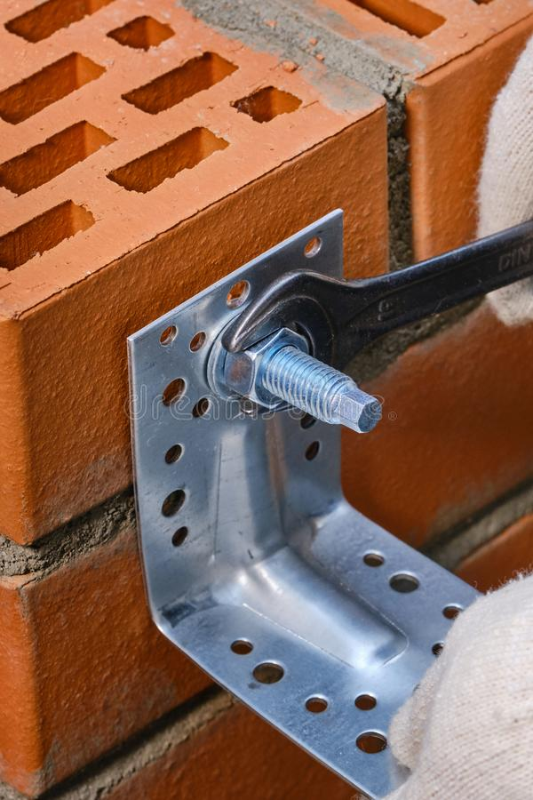 Red hollow brick. Brickwork. Installation of a chemical anchor using a special tool - resin, sleeve and metal angle. Technological. Stage of installation of royalty free stock photo