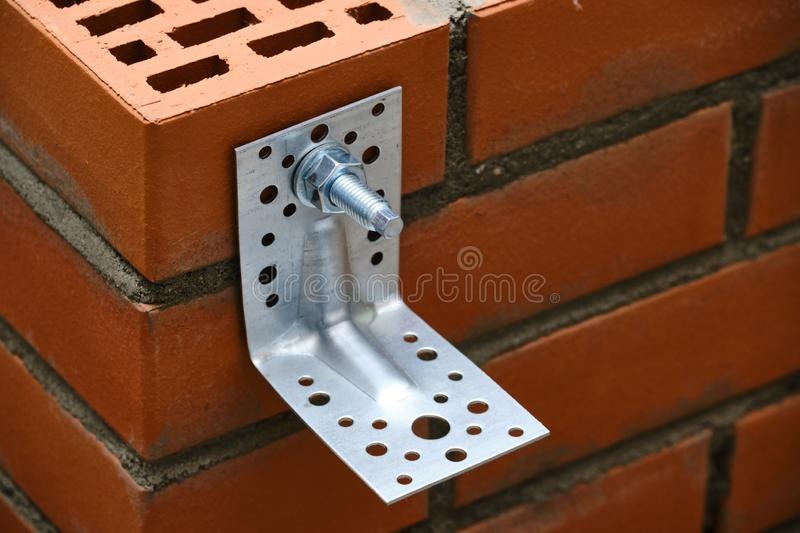 Red hollow brick. Brickwork. Installation of a chemical anchor using a special tool - resin, sleeve and metal angle. Technological. Stage of installation of stock photos