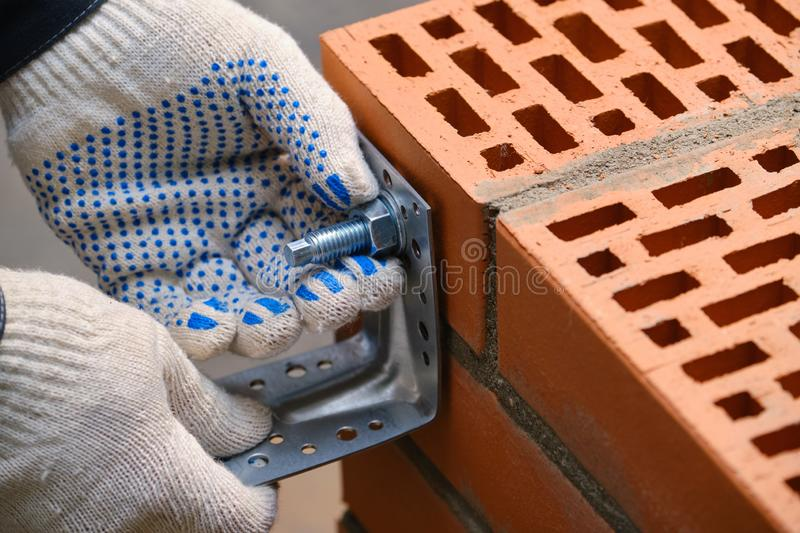 Red hollow brick. Brickwork. Installation of a chemical anchor using a special tool - resin, sleeve and metal angle. Technological. Stage of installation of royalty free stock images