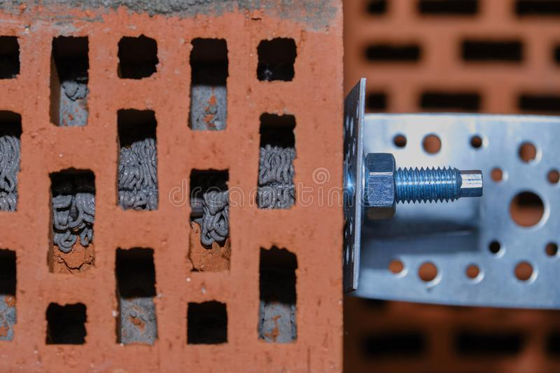 Red hollow brick. Brickwork. Installation of a chemical anchor using a special tool - resin, sleeve and metal angle. Technological. Stage of installation of royalty free stock photos